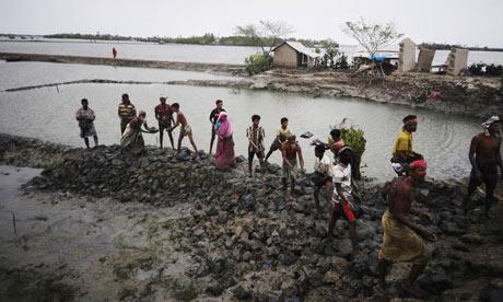 Bangladeshi villagers repair a vital flood-protecting embankment