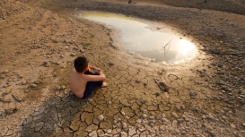 Water crisis:  Child sitting on cracked earth near drying water