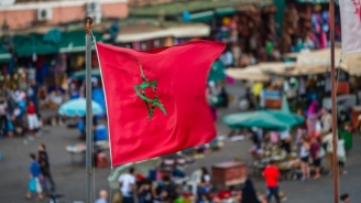 Moroccan flag over Djemaa El Fna Square in Marrakech, Morocco