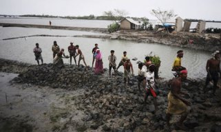 Bangladeshi villagers repair a vital flood-protecting embankment