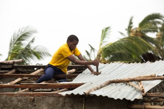 IDAI Aftermath - A man fixes the roof of his house in Praia Nova