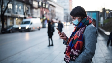 young woman with face mask using smartphone-GND-iStock