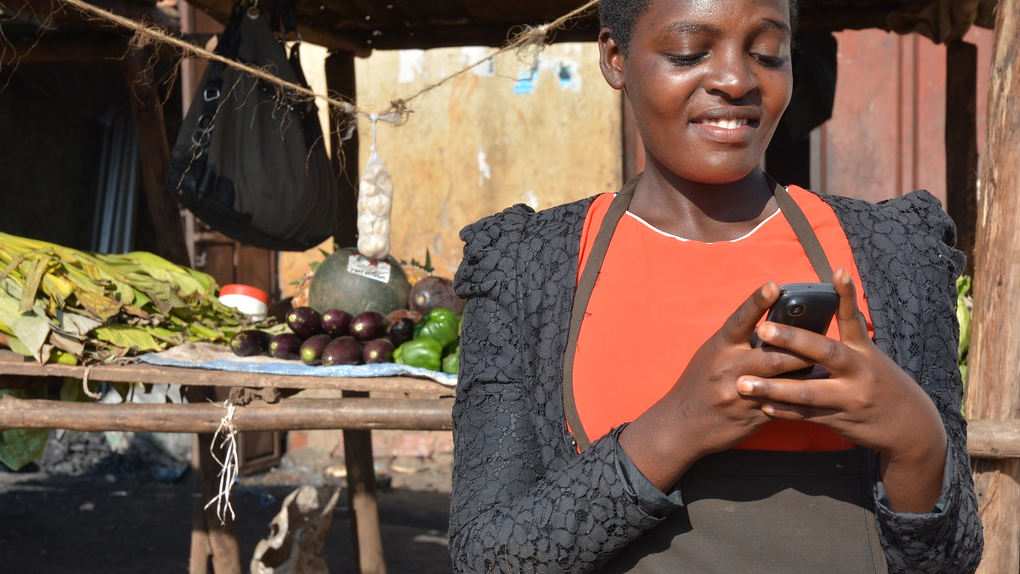 ug-business owner uses her phone for mobile banking-Anna Koblanck IFC
